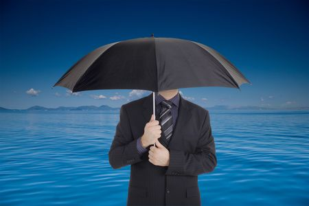 A businessman holding an umbrella covering his face photo