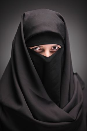 cultural and ethnic clothing: A veiled woman isolated on a black background