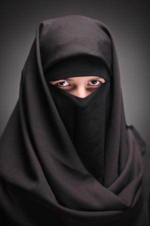 veiled: A veiled woman isolated on a black background