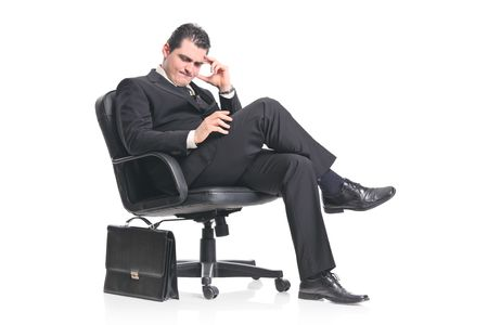 A worried businessman sitting in an office chair isolated on a white background photo