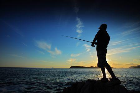 hombre pescando: El hombre pesca en la puesta de sol