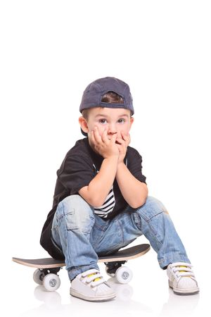boy sitting: Little child sitting on a skateboard isolated on white background Stock Photo