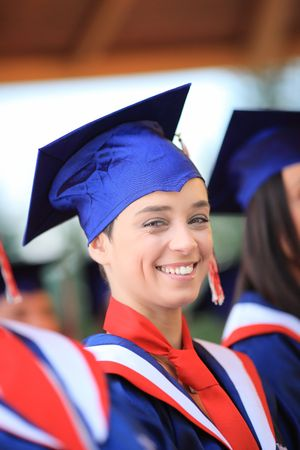 attired: Happy graduating student wearing cap and gown Stock Photo