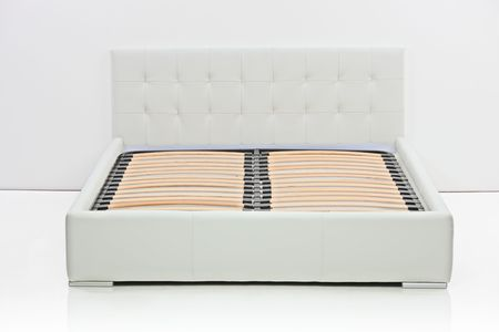 A view of a modern bed in an empty room photo