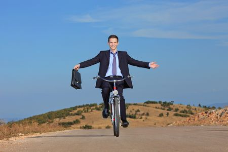 Carefree businessman holding a briefcase and riding a bicycle outdoors