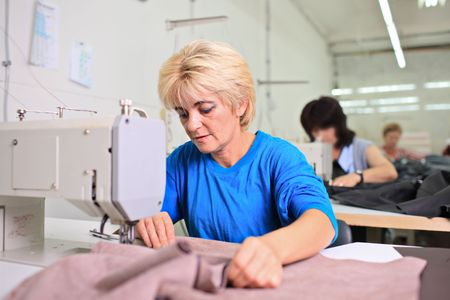 textile industry: Tailor working at a textile factory Stock Photo