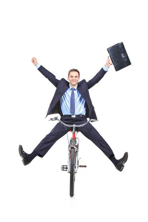 Happy young businessman on a bicycle isolated against white background photo