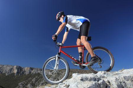 cyclists: A man riding a mountain bike downhill style
