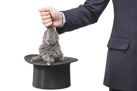 Businessman pulling a rabbit out of a silk top hat photo
