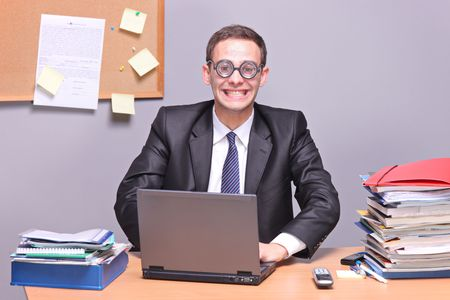 Nerdy businessman working on a laptop in the office photo
