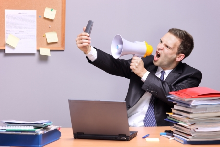 loudness: Angry businessman in an office, shouting on a megaphone, holding a mobile phone in the hand Stock Photo