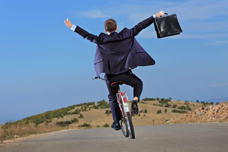 free riding: Carefree businessman holding a  briefcase and riding a bicycle outdoors