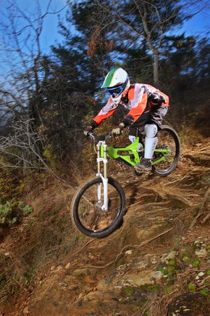 A young man riding a mountain bike downhill style photo