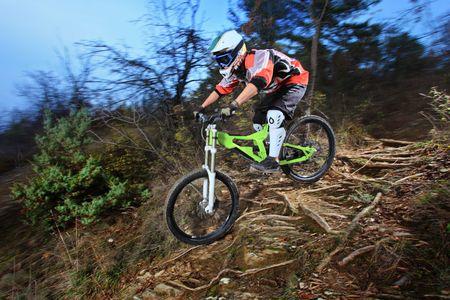 A young man riding a mountain bike downhill style photo