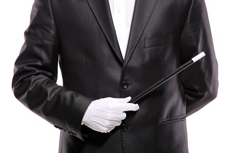 gloved: A magician in a suit holding a magic wand isolated on white background Stock Photo