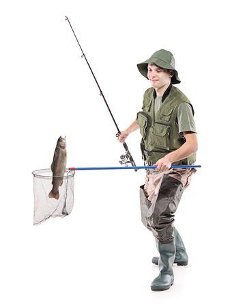 hand crank: Joven pescador poniendo un pez en una red de pescar aislado sobre fondo blanco