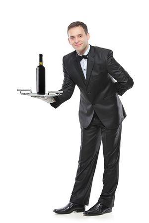 meseros: Persona joven sosteniendo una bandeja con un vino tinto sobre ella, aislado sobre fondo blanco Foto de archivo