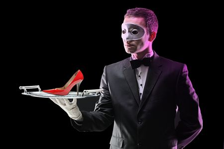 Buttler with a mask holding a tray with high heel on it photo