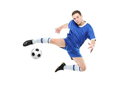 foot gear: Soccer player with a ball in action isolated on white background