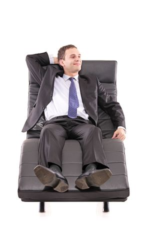 ergonomic: A happy  businessman taking a rest on a sofa isolated on white
