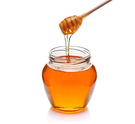 Pot honing met houten drizzler geïsoleerd op witte achtergrond  Stockfoto