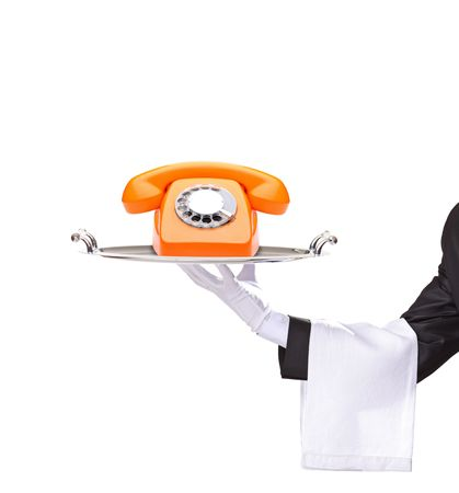 serving tray: Hand holding a silver tray with an orange telephone on it isolated on white background