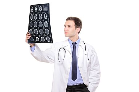 A young medical doctor analyzing a CT scan isolated on white background photo