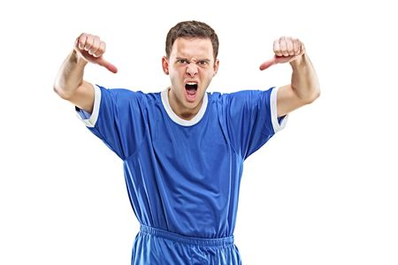An angry soccer player shouting and giving thumbs down isolated on white background photo