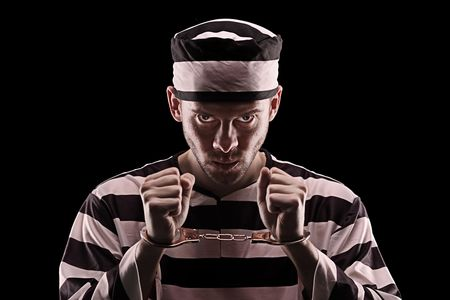 Angry prisoner with handcuffs isolated on black background photo