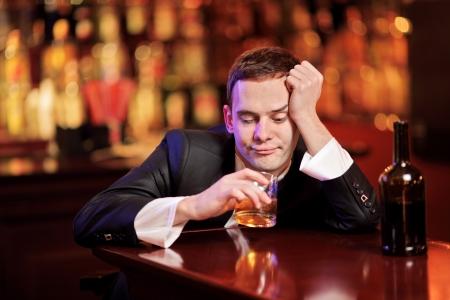 Joven borracho bebiendo whisky en la barra de