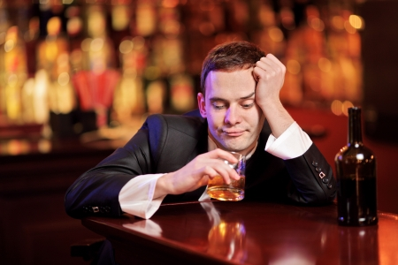 drunken: Young drunk man drinking whiskey in the bar
