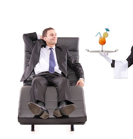 Young businessman relaxing on a sofa while the butler serving a cocktail isolated on white photo