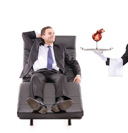 Young businessman relaxing on a sofa while the butler serving a red wine glass isolated on white photo