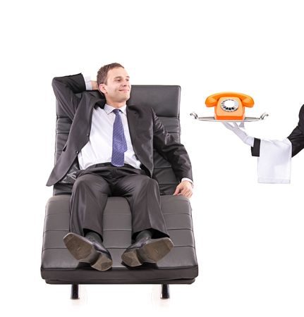 Young businessman relaxing on a sofa while the butler holding a telephone isolated on white photo