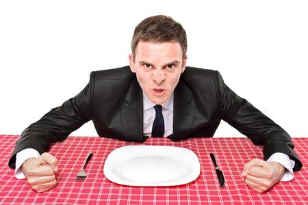 Un hombre enojado esperando su comida en un restaurante Foto de archivo