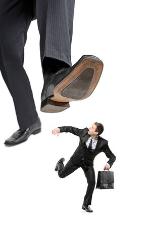 An affraid businessman running away from a big foot isolated on white background photo
