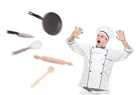 A view of flying kitchen utensils towards stunned chef isolated on white background Stock Photo - 6822677