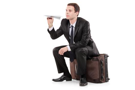 A businessman sitting on a luggage and holding a paper toy plane isolated on white background photo