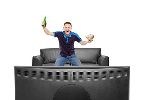 Sport fan with beer bottle and popcorn in his hands wayching a match on TV isolated on white background photo