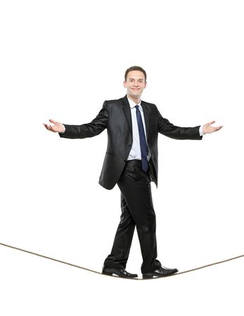 wire rope: A business man walking on a high tightrope isolated on white background