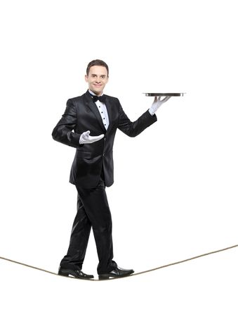 servant: A young butler carrying a tray and walking on a rope isolated on white background
