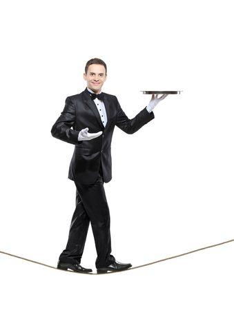 sirvientes: Un mayordomo joven llevando una bandeja y caminar sobre una cuerda aislada sobre fondo blanco Foto de archivo