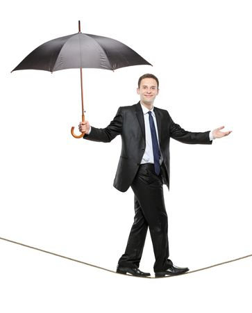 steadiness: A perosn holding an umbrella and walking on a high tightrope isolated on white background Stock Photo