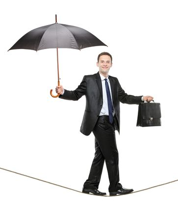 A business person holding an umbrella and a briefcase walking on a tightrope isolated on white background photo