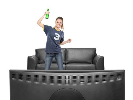 Excited girl watching sport on a TV isolated on white background photo