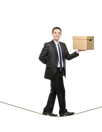 walk board: A businessman holding a paper box and walking on a rope isolated on white background