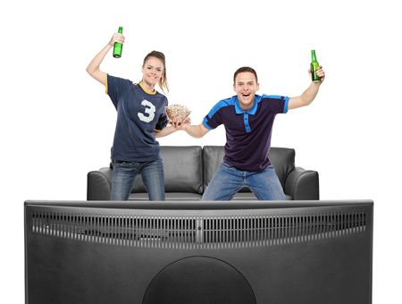 Excited boy and girl watching sport on a TV isolated on white background photo