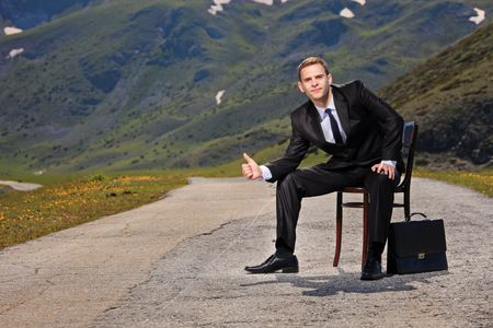 Businessman hitchhiking on a highway  photo