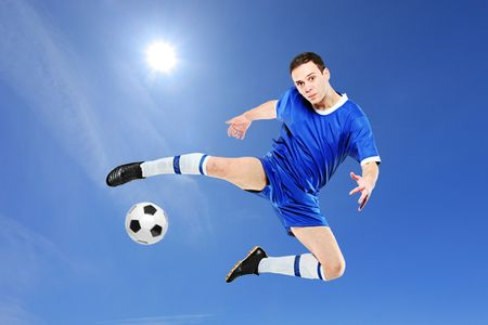 Soccer player with a ball in action against blue sky photo