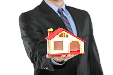 Real estate agent holding a model house in a hand isolated on a white background photo